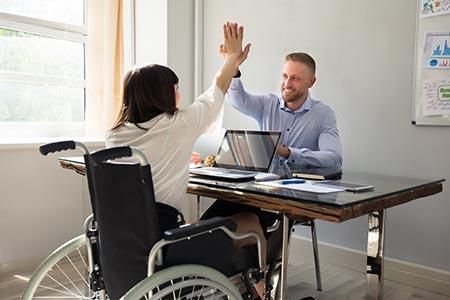 Une handicapée en fauteuil et un homme se tapent dans la main autour dans un bureau