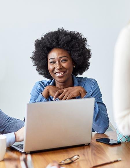 Femme noire souriant derrière un ordinateur portable