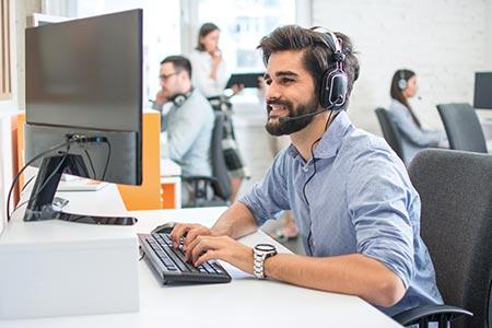 Un homme avec un micro casque assurant le SAV dans un call center