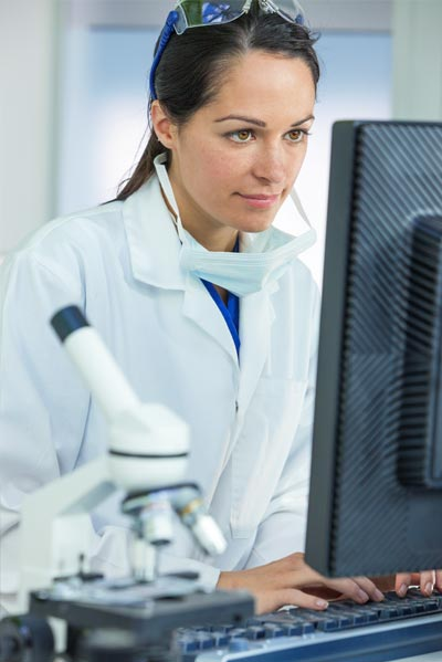 Une laborantine devant un écran d'ordinateur
