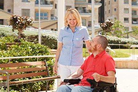 Une soignante auprès d'un homme en chaise roulante - Teranga Software NETVie