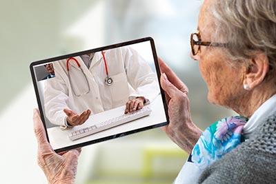 Femme du troisieme âge faisant une téléconsultation sur une tablette tactile