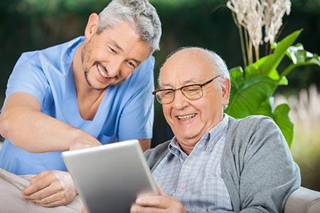 une jeune homme et une personne âgée rient devant une tablette tactile