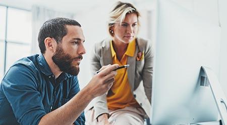 un jeune homme et une femme regarde ensemble un écran d'ordinateur